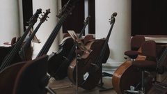 Dolly shot of few cellos on scene in classical music style concert hall Stock Footage