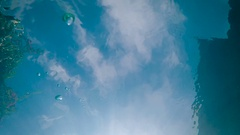 View of blue sky and white clouds from the bottom through the quaking water Stock Footage