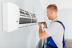 Technician Fixing Air Conditioner Stock Photos