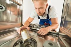 Man In Overall Repairing Dishwasher Stock Photos