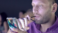 Young man texting on smartphone and drinking cocktail in bar at night Stock Footage