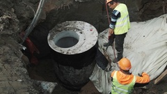 Builders in hard hats scorch concrete chamber manhole ring with flamethrower Stock Footage