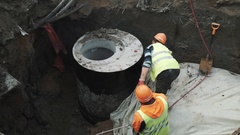 Workers in hard hats scorch concrete chamber manhole ring with flamethrower Stock Footage