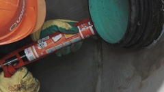 Close up worker in hard hat use sealant on plastic tube immured in concrete Stock Footage
