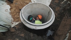 Worker in hard hat inside of concrete manhole ring using sealant on plastic pipe Stock Footage