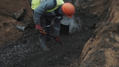 Slowmotion worker in orange hard hat throws macadam with shovel in ditch Stock Footage