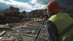 Worker in hard hat use theodolite and give gesture instructions to partners Stock Footage