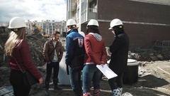 Men and women in hard hats speaking near concrete manhole ring at building site Stock Footage