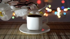 Cup of coffee on a bamboo napkin on a background of white orchids Stock Footage
