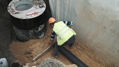 Builder in hard hat beat long plastic pipe with sledge hammer in trench Stock Footage