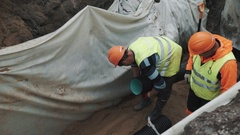 Worker in hard hat hold long plastic pipe between legs in ditch at building site Stock Footage