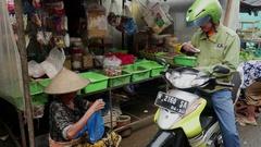 Biker has bought goods in the food market in Jakarta, Indonesia. Stock Footage