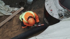 Worker in hard hat use sealant on plastic pipe in concrete manhole ring in ditch Stock Footage
