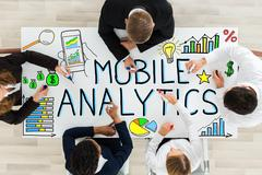 Businesspeople Drawing Mobile Analytic Concept On Desk Stock Photos