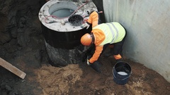 Worker in hard hat applying tar on plastic tube in concrete chamber manhole ring Stock Footage