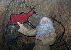 The bearded hermit in sackcloth shows painting animals on cave walls. Stock Photos