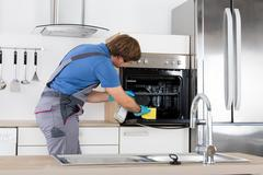 Man In Overall Cleaning Oven Stock Photos