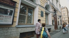 Tracking shot people walking along old city street in summertime on sunny day Stock Footage