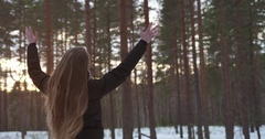Slow motion of teenage girl with raised hands in winter pine forest freedom Stock Footage
