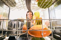 Happy Woman Arranging Plates In Dishwasher Stock Photos