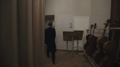 Tracking shot man in black tail-coat walking behind scene in concert hall Stock Footage