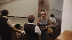 Woman with ticket in hand speaks to usher on staircase in old style concert hall Stock Footage