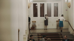 Usher woman showing pamfets to people in old classic style concert hall interior Stock Footage