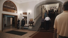 Group of people walk up staircase in old style concert hall corridor interior Stock Footage