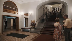 People walk up a footway in old style classical concert hall corridor interior Stock Footage