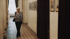 Old woman observes pictures on wall of corridor in old classic style interior Stock Footage