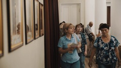People walking along corridor in classic style interior with pictures on wall Stock Footage