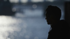 4K Silhouette of a young male looking out to the river ahead Stock Footage
