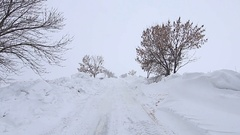 Walking on snowy road with snowdrifts in the cold winter, POV Steady cam shot Stock Footage