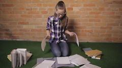 Teen girl factitiously doing home task sitting on a floor Stock Footage