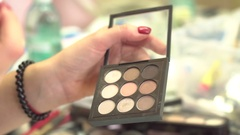 Make-up artist taking eye shadows from multicolor make-up eyeshadows palette in Stock Footage