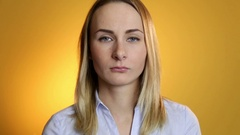 A cute young white woman makes a sad face on a yellow background Stock Footage