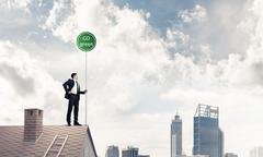 Businessman in suit on house top with ecology concept signboard Stock Photos