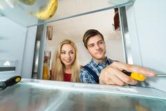 Woman Looking At Male Worker Repairing Refrigerator Stock Photos