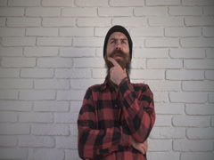 Thoughtful man with a beard stroking his beard, folded his arms across his chest Stock Footage