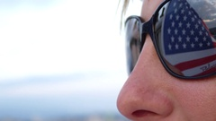 CLOSE UP: American flag waving in wind, reflecting in young woman's sunglasses Stock Footage
