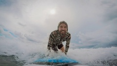 Young man rides a surfboard, catch a small ocean wave, and then falls into the Stock Footage