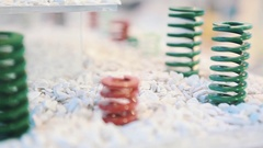 Colorful metal springs stand on white marble macadam stones on display Stock Footage