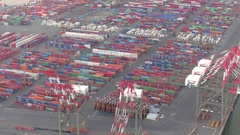 AERIAL: Forklift trucks unloading colorful shipping containers in sea port Stock Footage