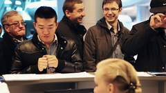 People in outerwear talk to manager on reseption of business center hall Stock Footage