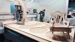 Wood router machine cutting pieces on display at business innovation exposition Stock Footage