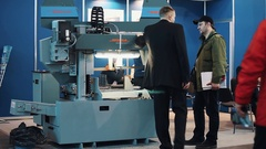 Man in suit and in coat discuss piece of machinery at business innovation show Stock Footage