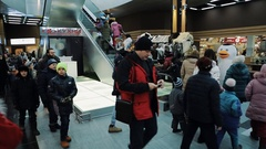 Kid crowd going up escalator in shopping mall. Christmas elf and penguin mascot Stock Footage