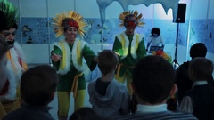 Christmas elfs in mohawk wigs entertaining kids in colorful light room Stock Footage