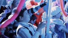 Boy kid crowd learning to make balloon animals, colorful lights Arkistovideo