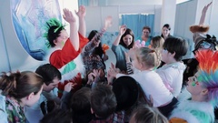 Christmas elfs in mohawk wigs gathering with kids in colorful light room Stock Footage
